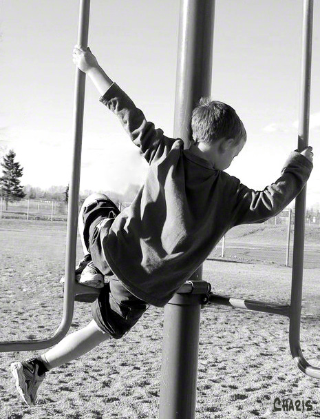 boy playing monkey bars bw